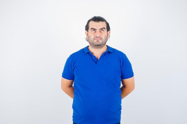 Man van middelbare leeftijd die handen achter rug in polot-shirt houdt en peinzend, vooraanzicht kijkt.
