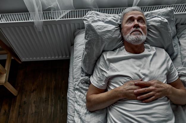 Man van middelbare leeftijd die in bed op een kussen ligt, met slapeloosheid, slaapstoornis. alleen thuis