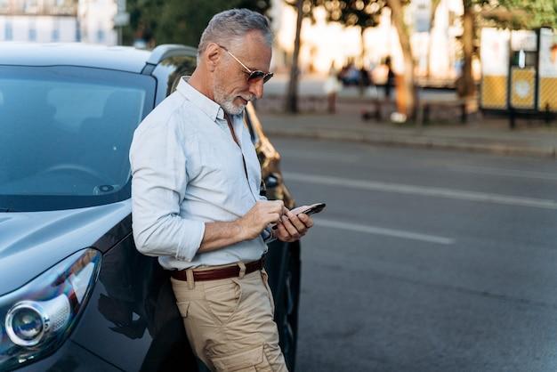 Man van middelbare leeftijd die in de buurt van zijn suv-auto staat en zijn smartphone gebruikt. portret van senior man buitenshuis.
