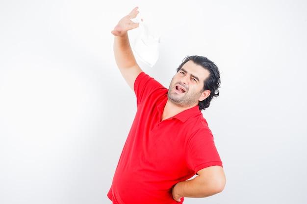 Man van middelbare leeftijd die servet opheft terwijl hij de hand op de heup in een rood t-shirt houdt en er attent uitziet. vooraanzicht.