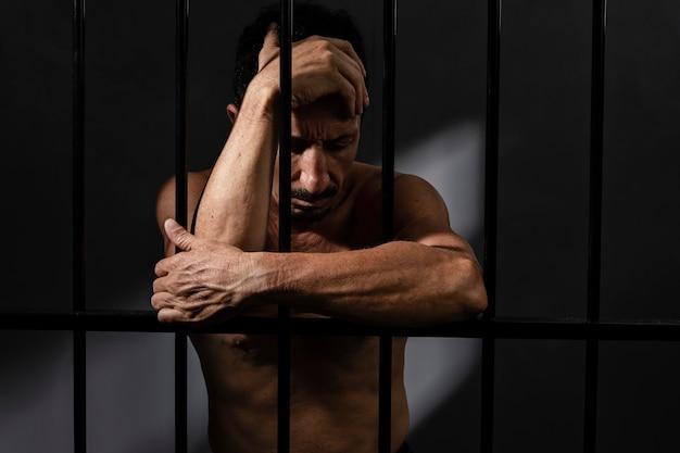Man van middelbare leeftijd die tijd doorbrengt in de gevangenis