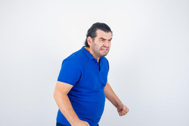 Man van middelbare leeftijd die weg in polot-shirt kijkt en woedend kijkt. vooraanzicht.