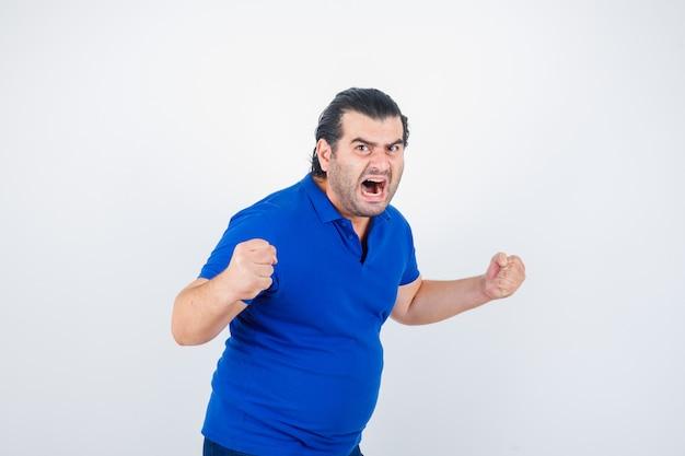 Man van middelbare leeftijd die winnaargebaar in polot-shirt toont en agressief kijkt. vooraanzicht.