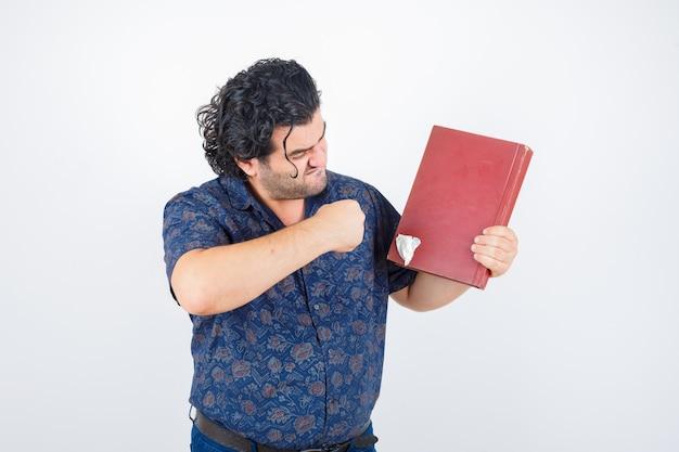 Man van middelbare leeftijd die zich klaarmaakt om boek in overhemd te slaan en boos, vooraanzicht kijkt.