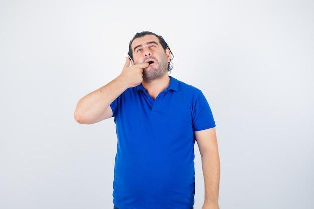 Man van middelbare leeftijd die zijn tanden in polot-shirt controleert en ongezellig kijkt. vooraanzicht.