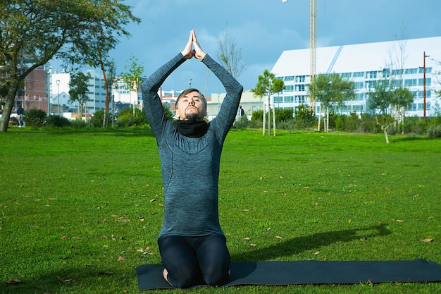 Man van middelbare leeftijd doet ademhaling, ontspanning, yoga, rekken, oefenen, trainen in het park met behulp van yogamat. natuurlijke yoga voor beginners. gezondheidszorg concept.