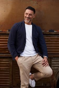 Man van middelbare leeftijd draagt lachend op een roestige gekleurde achtergrond