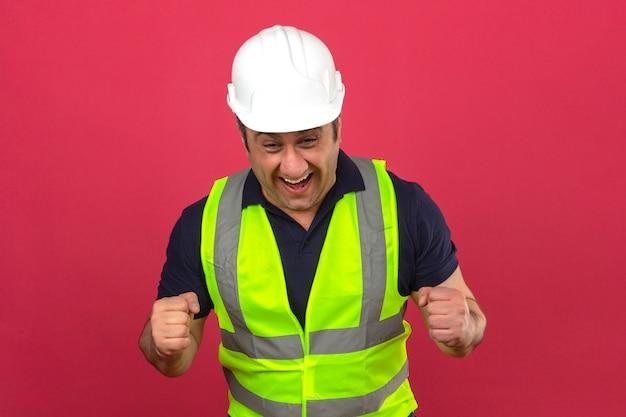 Man van middelbare leeftijd dragen bouw gele vest en helm blij opgewonden opgewekt het verhogen van zijn vuisten over geïsoleerde roze muur