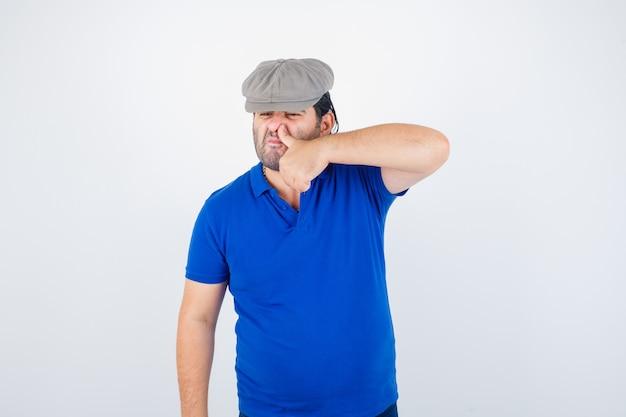 Man van middelbare leeftijd duim op neus in polo t-shirt, klimop hoed te drukken en ongezellig op zoek