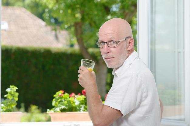 Man van middelbare leeftijd een drankje sinaasappelsap