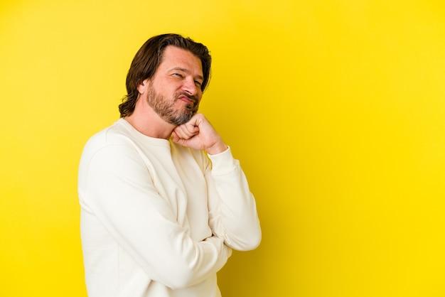 Man van middelbare leeftijd geïsoleerd op gele muur glimlachend gelukkig en zelfverzekerd, kin met hand aanraken
