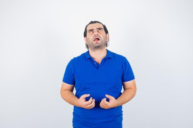 Man van middelbare leeftijd hand in hand op agressieve manier in polo t-shirt en op zoek verveeld. vooraanzicht.