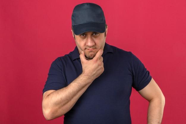 Man van middelbare leeftijd het dragen van poloshirt en pet raken kin terwijl het denken en met ernstige gezicht over geïsoleerde roze muur
