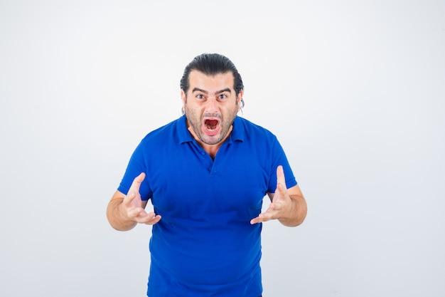 Man van middelbare leeftijd houden handen op agressieve manier in blauw t-shirt en kijkt boos. vooraanzicht.