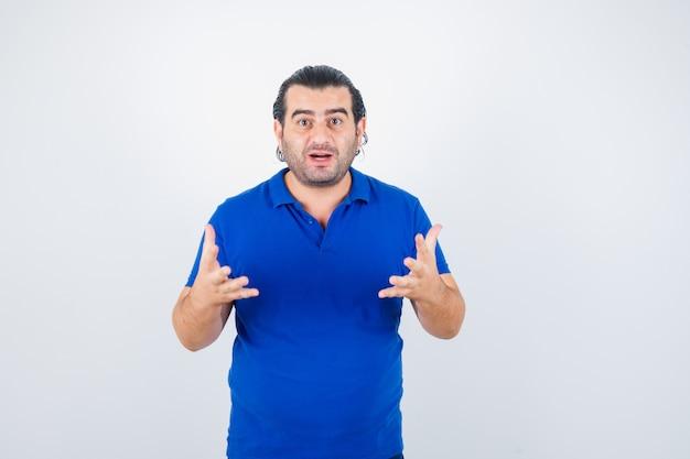 Man van middelbare leeftijd houden handen op agressieve manier in blauw t-shirt en kijkt verbaasd. vooraanzicht.