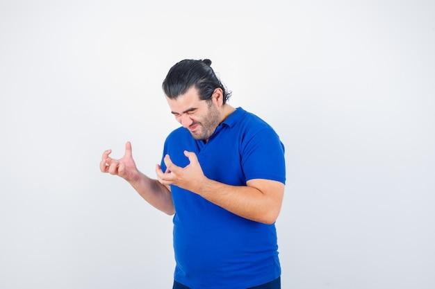 Man van middelbare leeftijd houden handen op agressieve manier in polot-shirt en kijkt boos. vooraanzicht.