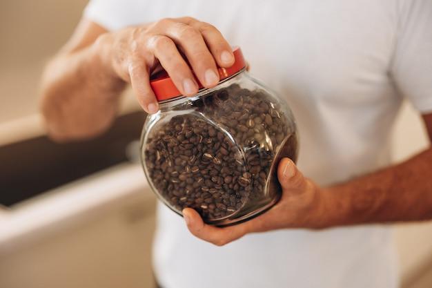 Man van middelbare leeftijd houdt een pot koffiebonen vast