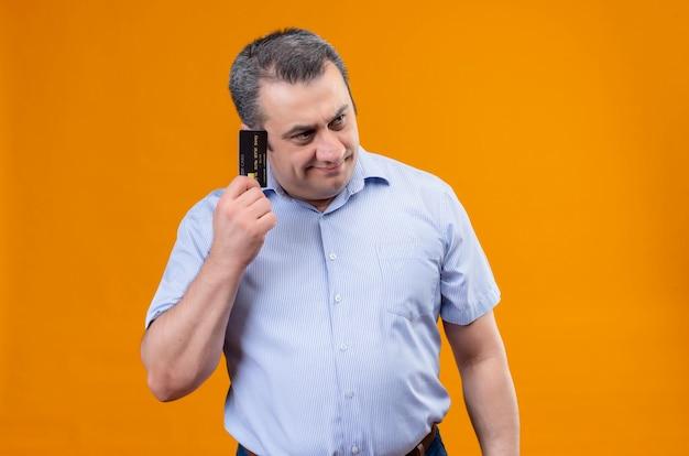 Man van middelbare leeftijd in blauw gestreept shirt na te denken over plannen met creditcard op een oranje achtergrond