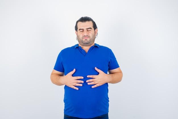 Man van middelbare leeftijd in blauw t-shirt hand in hand op de buik en op zoek naar rustige, vooraanzicht.
