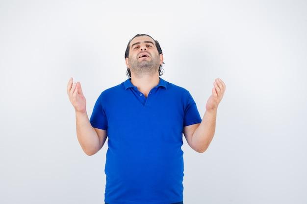 Man van middelbare leeftijd in blauw t-shirt handen opheffen om te bidden en op zoek naar hoopvol, vooraanzicht.