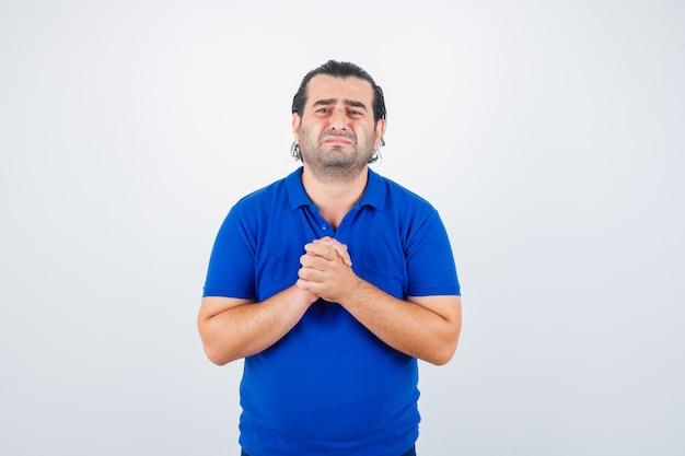 Man van middelbare leeftijd in blauw t-shirt met gevouwen handen in smekend gebaar en op zoek naar hoopvol, vooraanzicht.