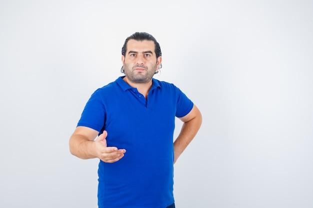 Man van middelbare leeftijd in blauw t-shirt uitrekken hand in vragend gebaar en op zoek naar zelfverzekerd, vooraanzicht.