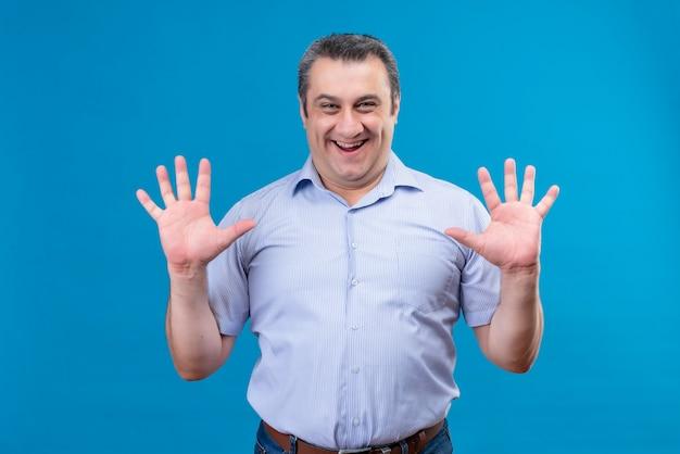 Man van middelbare leeftijd in blauw verticaal gestreept overhemd met blij gezicht dat en met vinger nummer tien op een blauwe achtergrond benadrukt