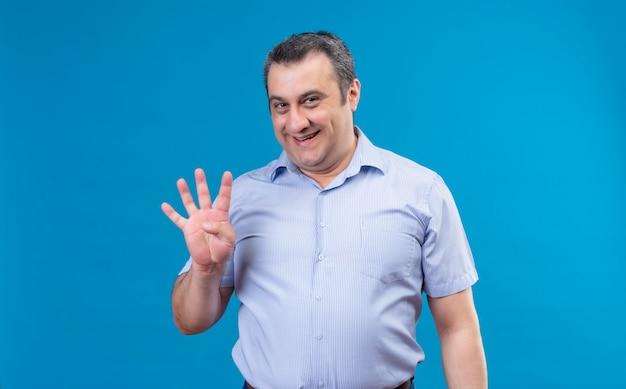 Man van middelbare leeftijd in blauw verticaal gestreept overhemd met blij gezicht dat en met vinger nummer vier op een blauwe achtergrond benadrukt