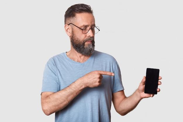 Man van middelbare leeftijd in grijs casual t-shirt, staat op de witte muur, wijzend met de vinger op het lege scherm van zijn smartphone, kijkend op het apparaat. kopieer ruimte.