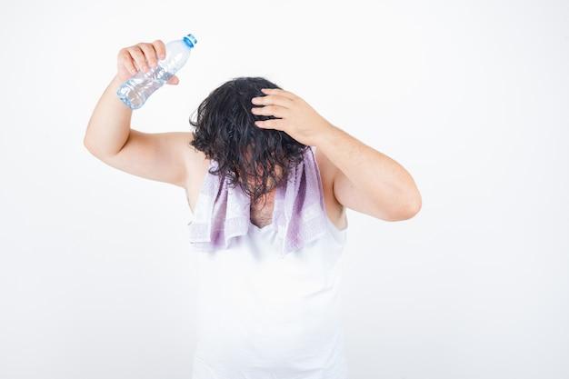 Man van middelbare leeftijd in mouwloos onderhemd, handdoek gietend water op het hoofd met fles en op zoek grappig, vooraanzicht.