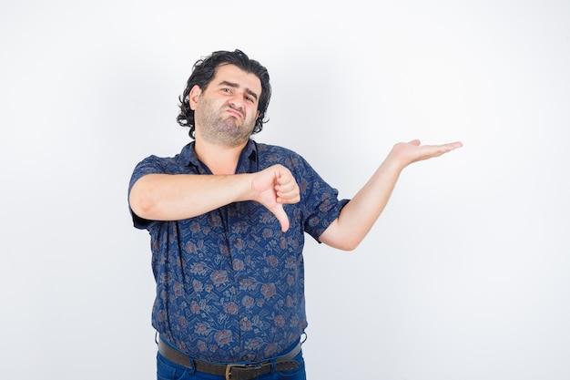 Man van middelbare leeftijd in overhemd die iets vasthoudt terwijl hij zijn duim laat zien en ontevreden kijkt, vooraanzicht.