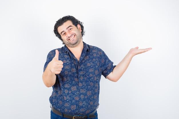 Man van middelbare leeftijd in overhemd die iets vasthoudt terwijl hij zijn duim toont en tevreden kijkt, vooraanzicht.
