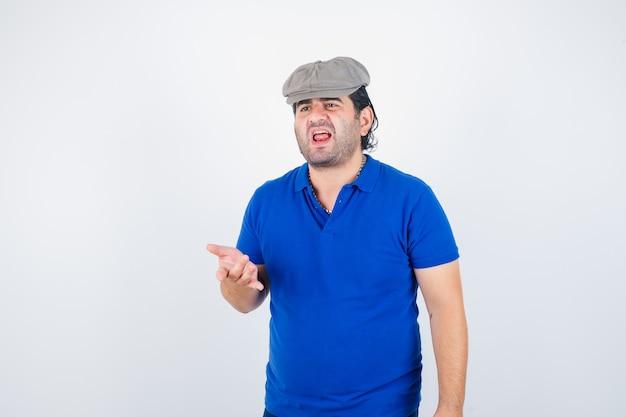 Man van middelbare leeftijd in polo t-shirt, klimop hoed agressief te wijzen