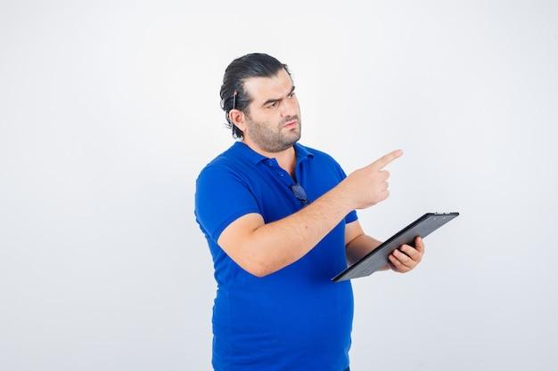 Man van middelbare leeftijd in polot-shirt met klembord terwijl hij naar rechts wijst en peinzend kijkt, vooraanzicht.