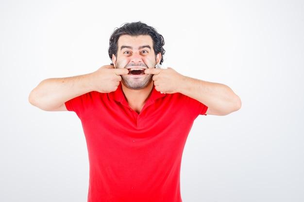 Man van middelbare leeftijd in rood t-shirt mond met handen opzij te trekken en grappig, vooraanzicht op zoek.