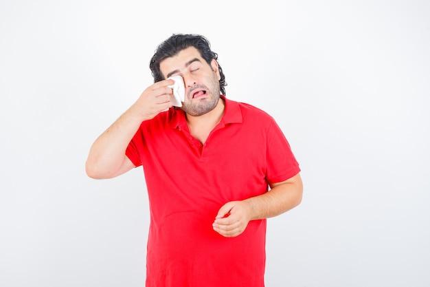 Man van middelbare leeftijd in rood t-shirt oog met servet afvegen terwijl huilen en op zoek beledigd, vooraanzicht.