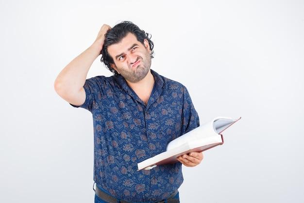 Man van middelbare leeftijd in shirt met boek terwijl hoofd krabben en op zoek attent, vooraanzicht.