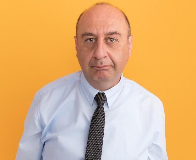 Man van middelbare leeftijd kijken naar voorzijde dragen witte t-shirt met stropdas geïsoleerd op oranje muur