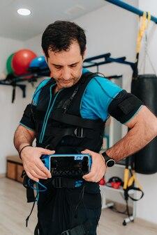 Man van middelbare leeftijd kijkt naar zijn ems-machine en draagt ook een elektrostimulatiepak