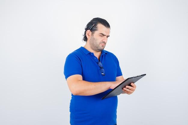 Man van middelbare leeftijd kijkt uit over documenten in klembord in polot-shirt en kijkt gericht. vooraanzicht.