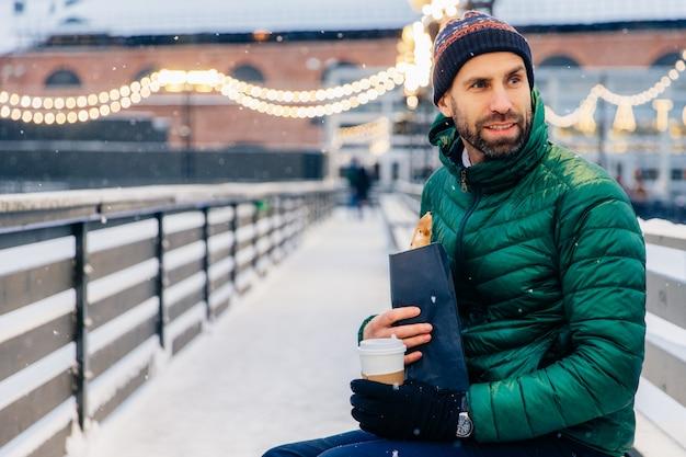 Man van middelbare leeftijd kijkt zorgvuldig opzij, heeft buiten een snack tijdens het winterweer, drinkt warme koffie en eet roll