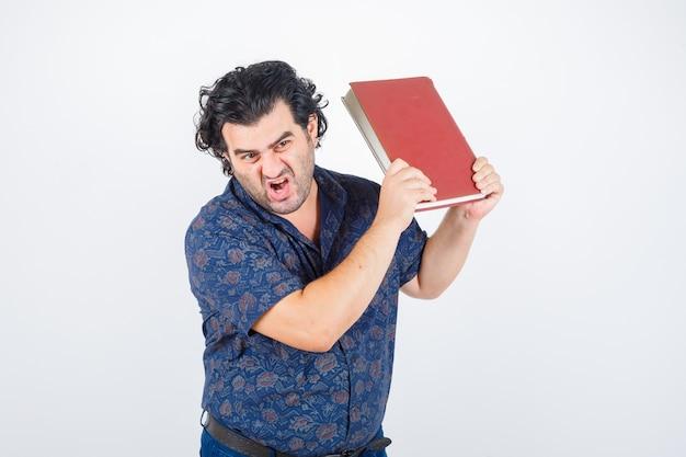 Man van middelbare leeftijd klaar om boek in shirt weg te gooien en op zoek boos. vooraanzicht.
