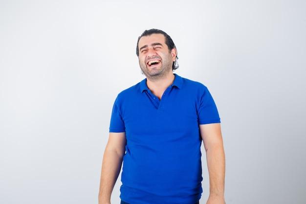 Man van middelbare leeftijd lachen in blauw t-shirt en op zoek vrolijk, vooraanzicht.