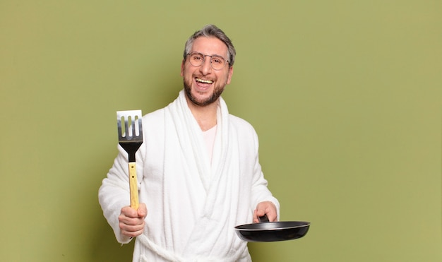 Man van middelbare leeftijd met badjas en leren koken met een pan