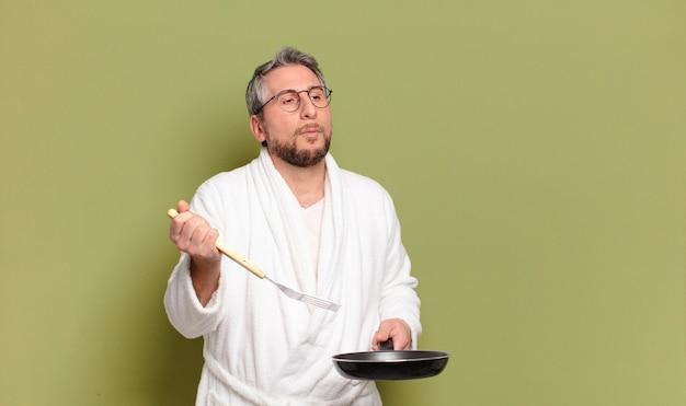 Man van middelbare leeftijd met badjas en leren koken met een pan Premium Foto