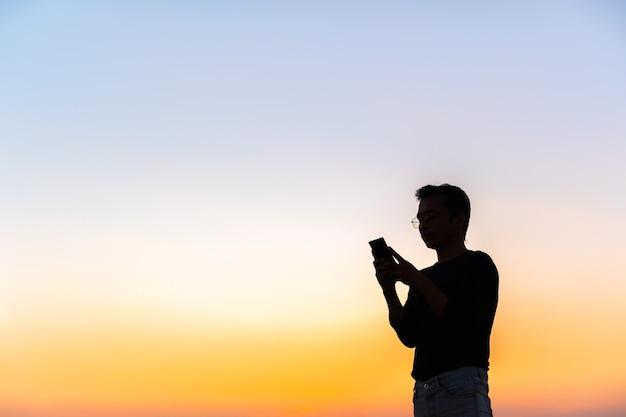Man van middelbare leeftijd met behulp van telefoon bij zonsondergang. een persoon neerkijkt op een smartphone met kopie ruimte.