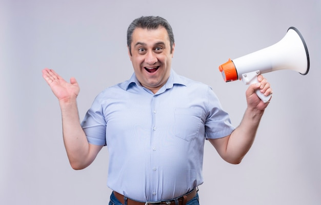 Man van middelbare leeftijd met blauwe verticale gestreepte shirt met megafoon terwijl staande op een witte achtergrond