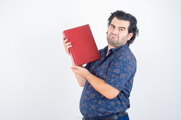 Man van middelbare leeftijd met boek over borst in overhemd en aarzelend, vooraanzicht op zoek.