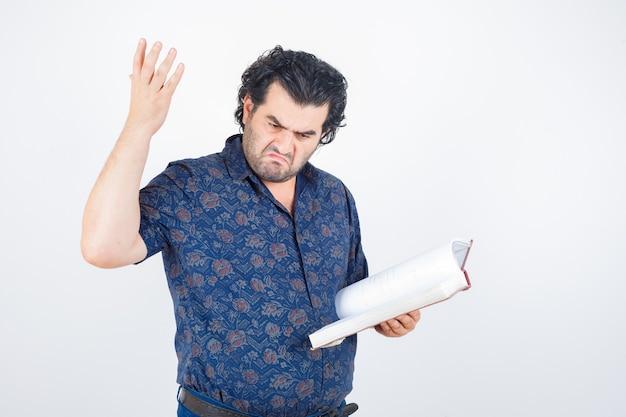 Man van middelbare leeftijd met boek terwijl het opheffen dient shirt in en kijkt boos, vooraanzicht.