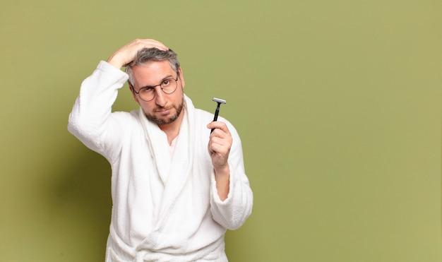 Man van middelbare leeftijd met een badjas en een scheermes